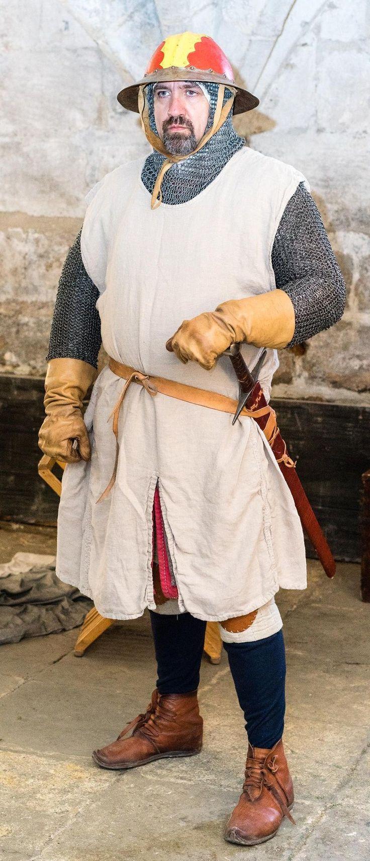 Een goed uitgeruste 13e eeuwse krijger. Boven zijn normale kleding draagt hij een gambeson (de rode stof nog net zichtbaar) en gewatteerde bovenbeenbescherming (ook wel 'cuisses' genoemd. Daar overheen draagt hij een maliënkolder, een wapenkleed en een mooi beschilderde ketelhelm.