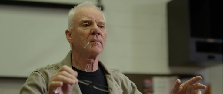 Mr. Simms (Malcolm McDowell) conducting the orchestra