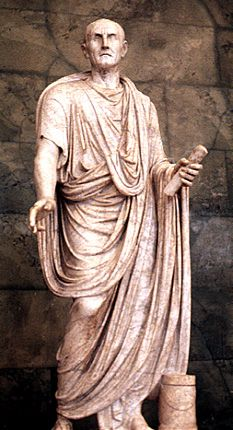 The man is wearing a tunic underneath (basic t-shirt garment) and on top, there is a toga (long dress-like garment that can be draped over the head and is rounded on the bottom)   Source: vroma