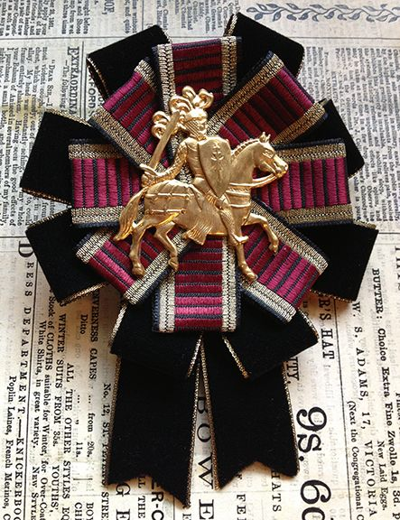 this rosette features a goldtone knight, surrounded by tiers of vintage striped ribbon (in tones of burgundy, gold, and black) and black velvet ribbon with a gold edge. this rosette measures approximately 4 inches wide and 5.5 inches tall. all mossbadger rosettes have a combination back so ...