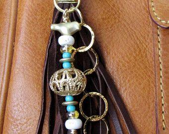 Ce pompon à la main peut être utilisé sur votre sac à main, sac à dos, fermeture éclair, partout où vous souhaitez ajouter un charme! Il est composé de Suède de peau de daim marron clair, perles de rocaille et perles plaquées or. Au total, le charme est d'environ 7,75 de long.