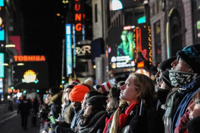 NEW YORK Tens of thousands of merrymakers converged on Times Square on Saturday evening, hours before the giant New Year's Eve ball makes its midnight descent, a century-old New York tradition unfolding this year under an unprecedented blanket of security.