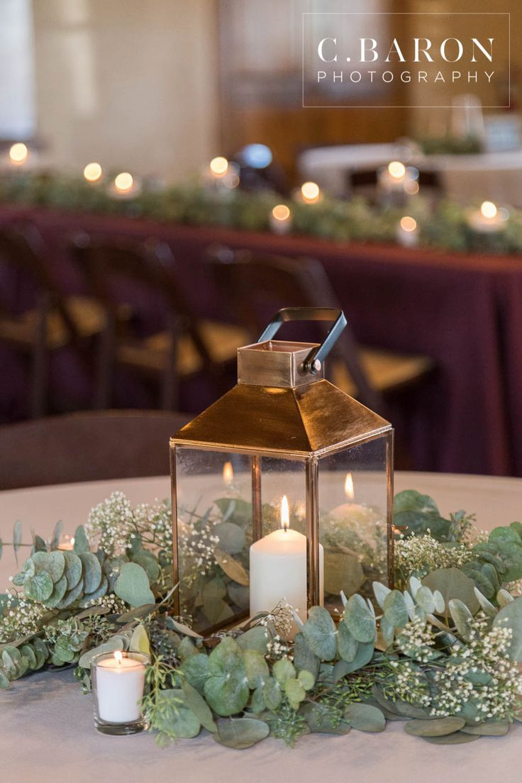 Gorgeous gold lantern as a wedding table centerpiece! Love the greenery  around it and the