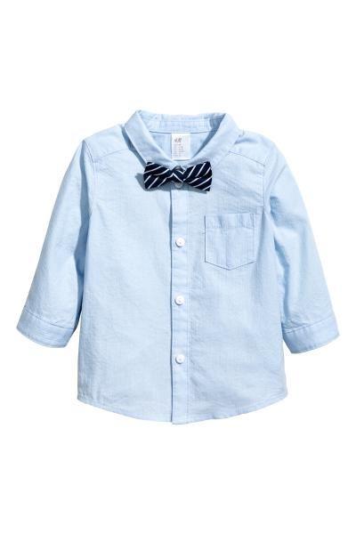コットンシャツ ボウタイ付き: ソフトなコットン素材の長袖シャツ。表面感のあるストライプ織り柄。片胸ポケット付き。フロントボタン。裾はゆるやかなラウンドカット。シャツと好相性のボウタイ付き。ボウタイは留め具付きで、首周りを調節できるゴムストラップが付いています。