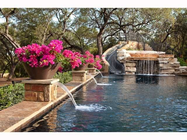 Classy way of doing a pool with slide... like this and the elevated bougainvillea as well