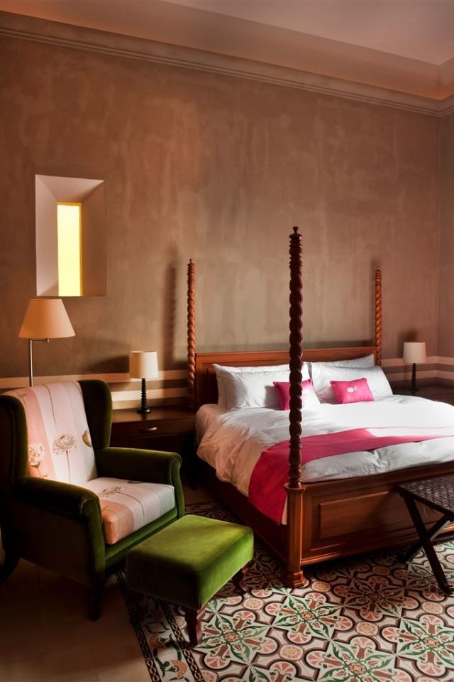 Located on Mexico's Yucatan Peninsula in Merida, Rosas & Xocolate is the place to visit for glam bedroom inspiration. With rich wooden furniture accented with pops of bright pink and green, along with geometric tile floor, this hotel's decor is nothing short of sumptuous.