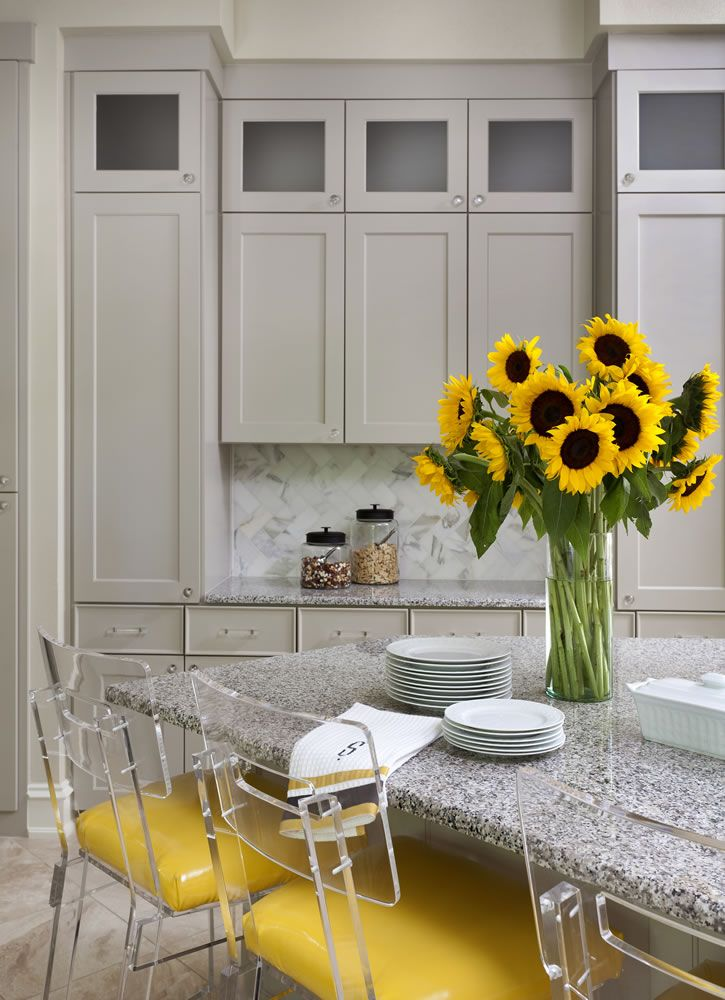 This kitchen states spring! Fresh flowers, especially sunflowers, adds a wonderful element to your kitchen. Merci!Those acrylic chairs...