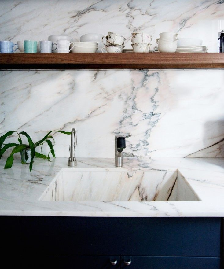 Pink marble kitchen worktop, set against dark blue kitchen cupboards and rustic wood shelving