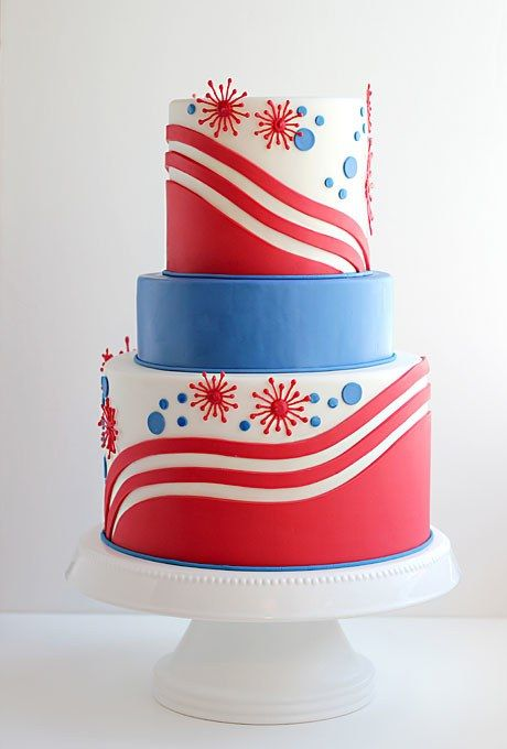 To make this festive, patriotic Fourth of July wedding cake, pastry artist and blogger Jessica Harris of Jessicakes handcut the wavy red stripes from modeling chocolate; the fireworks were created by meticulously piping melted chocolate onto wax paper in the shape of starbursts. Once the chocolate hardened, Jessica carefully lifted them from the wax paper and affixed the fireworks to the cake tiers using additional melted chocolate. The inside of the confection sounds as tasty as the overall…