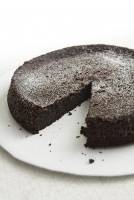 Chocolate olive oil cake (image: colour photo of dark brown round cake on white plate, one slice taken, a few crumbs on plate, white background)