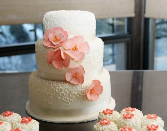 White three tier wedding cake with champagne ribbon trim, peach floral accents and coordinated cupcakes - #wedding #weddingcake