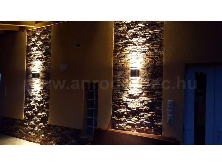 Szögletes alakú, szürke színű Kanlux Zew lámpatestek külső világításhoz.   A kőburkolattal borított homlokzaton helyezkednek el, felette viszont tető védi a lámpákat az esőtől és a nagyobb záporoktól.