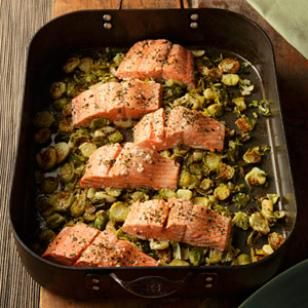 Roasting salmon on top of Brussels sprouts and garlic, flavored with wine and fresh oregano, is a meal that is simple enough for a weeknight meal yet sophisticated enough to serve to company.