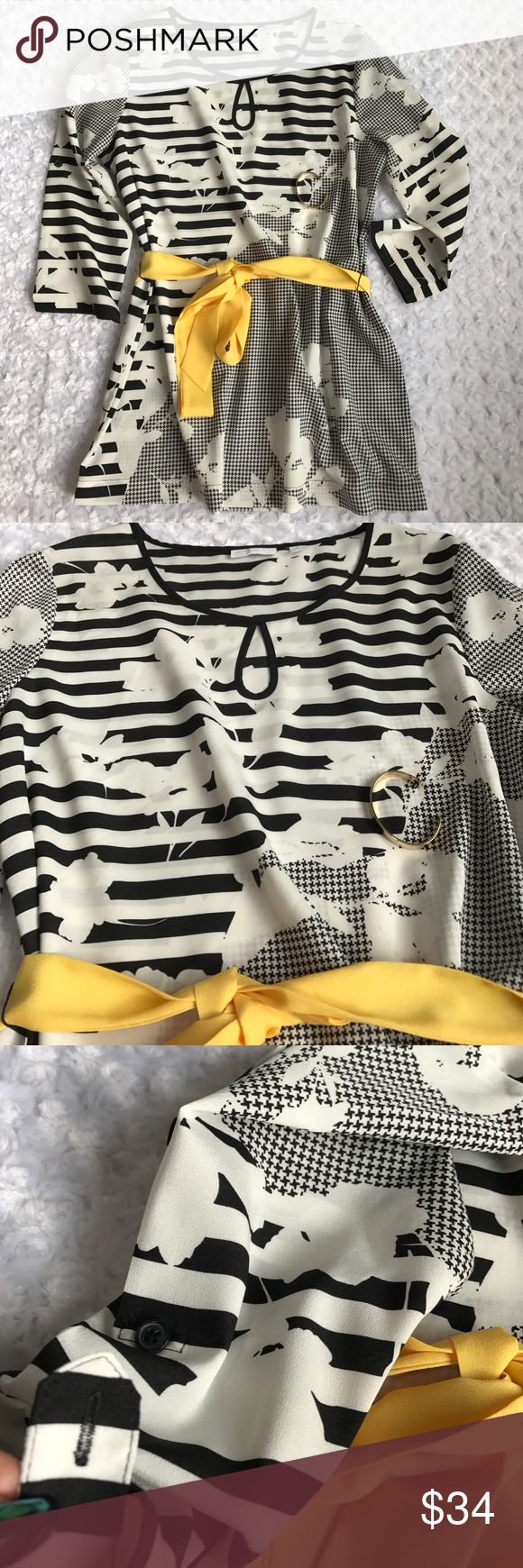 """•51• NEW YORK & CO BLACK WHITE TUNIC TOP If you love tunics like me: ❤️ This has a beautiful floral print with a twist of stripes and houndstooth. 3/4 sleeves with tab a button to shorten. Round neck with keyhole. The yellow belt is such a great accent color. What's nice is you can always add your own color belt to this. Length 28"""" Bust 20"""" Waist 20"""". Polyester. New York & Company Tops"""