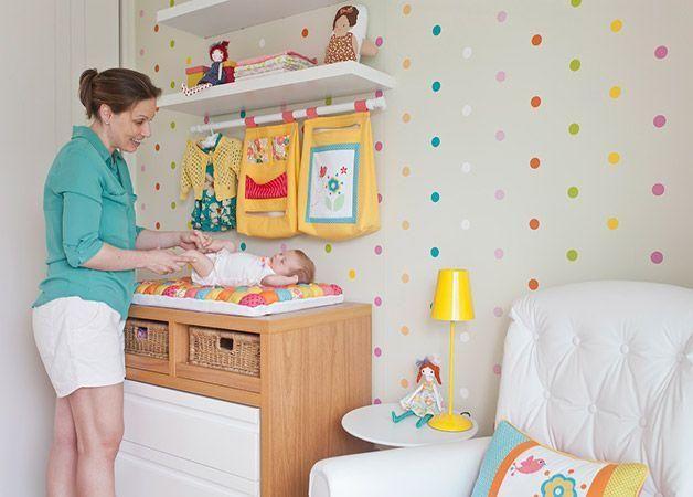 Papel de parede de bolinhas, estante e trocador num mesmo móvel