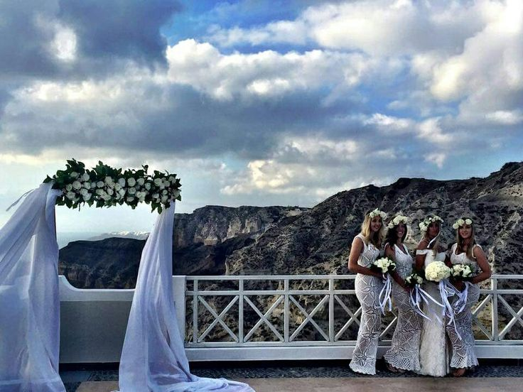 Wedding in santorini, bride and bridesmaids,  bridal bouquet with white Equador roses, wedding arch with ribbons www.santoweddingsbymk.com