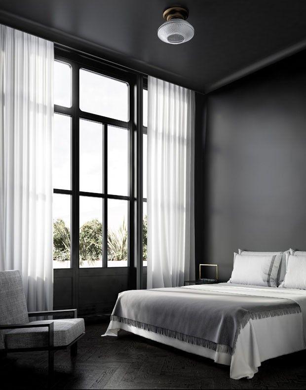 Quarto com parede preta é para amar! A sobriedade e o minimalismo dominam a decoração deste apartamento. O piso é de madeira escura e as esquadrias também. O contraste fica por conta da cortinha e jogo de cama branco. Clique para ver o apartamento completo.
