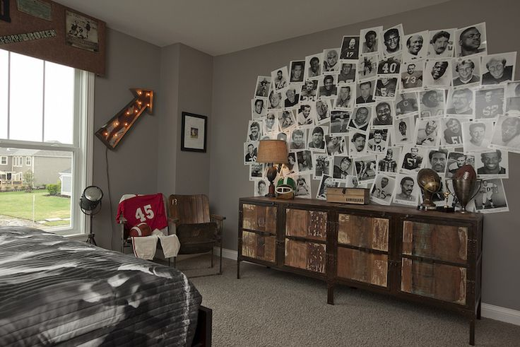 Football themed kid's room features vintage, black and white photos of football players over distressed dresser next to vintage stadium seats accented with football jerseys beside window dressed in cork cornice box decorated with football memorabilia alongside vintage sign.