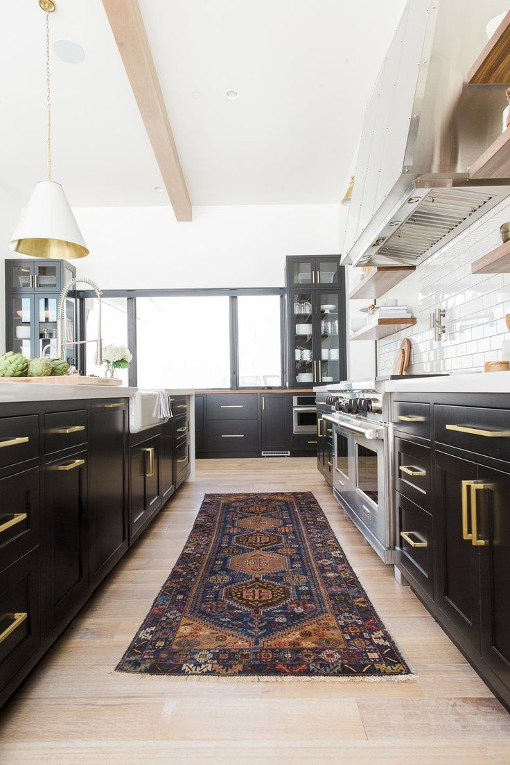 Black and white kitchen with bold brass hardware, light hardwood floors and a vintage Persian runner for color and texture.