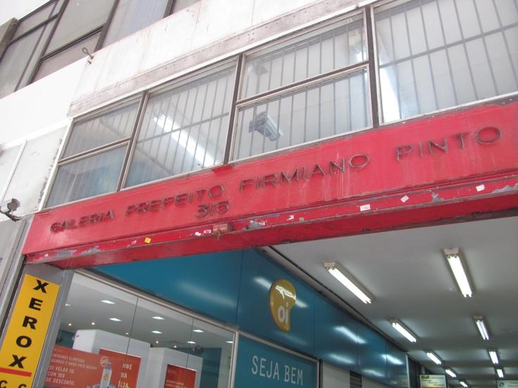 Inscrição em metal que sinaliza o nome e o número da Galeria Prefeito Firmiano Pinto.