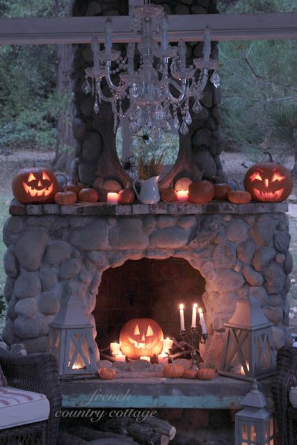 Gorgeous, cozy, warm and comfy! Outdoor fireplace with fall decorations and Halloween Jack-O-Lanterns from Courtney at FRENCH COUNTRY COTTAGE: Feathered Nest Friday. LOVE it! Check out the chandelier too!