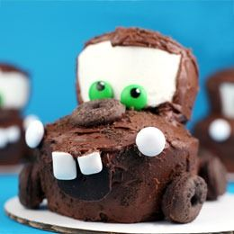 tow-mater-cupcake  1 box cake mix 2 16 oz cans of milk chocolate frosting 16 oz can of vanilla frosting 6 cup large muffin baking pan 12 cup regular size cupcake baking pan 4.44 oz box of Keebler Fudge Shoppe Grasshopper Cookies (100 Calorie Right Bites) Ziploc bag 12 White M&M's candies (headlights) 12 Green M&M's candies (eyes) 6 Eclipse gum pieces (teeth) 6 inch cardboard cake boards Black edible ink pen Toothpicks