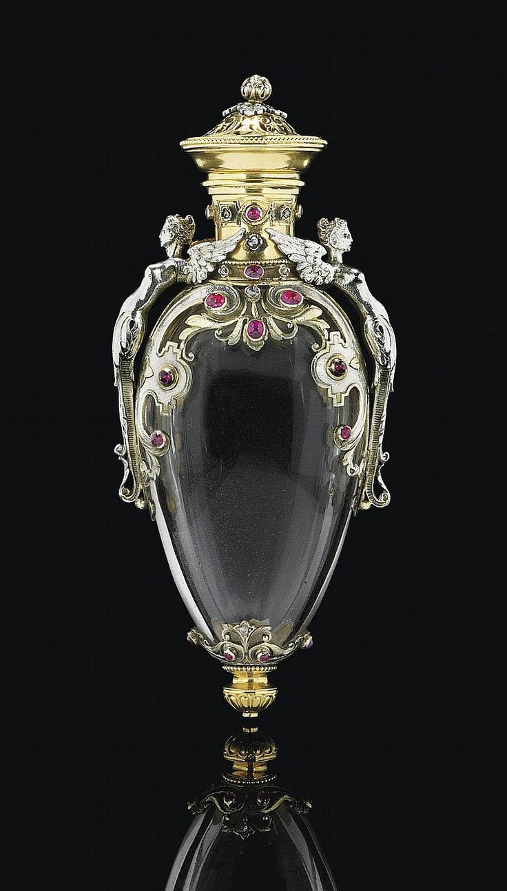 A FRENCH TWO-COLOUR GOLD AND GEM-SET ROCK-CRYSTAL SCENT-BOTTLE <br />CIRCA 1870, MAKER'S MARK INDISTINCT, ATTRIBUTED TO LES FRERES FANNIERE <br />The compressed ovoid rock crystal body with two-colour gold foliage and strapwork mounts, set with ruby cabochons and rose cut diamonds, with female-capped foliage handles and pierced lid with beaded border and leafy knop, the lower body with baluster knop, <i>marked on cover and near handle, the neck with scratched inventory number 'D2594'</i><br…