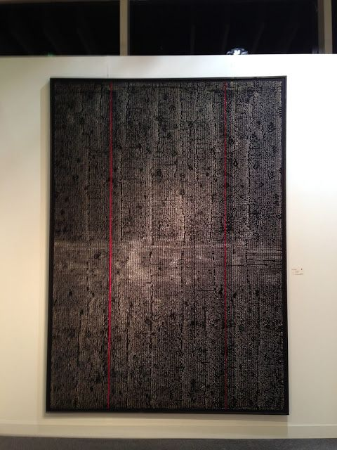 """Uemae. This nearly 7 foot tall piece is entirely hand stitched in 1/4 """" stitches with white thread on black fabric. The stitches run horizontally. There are spaces left that form verticals which evoke a feeling of city buildings glistening at night. The red stripes are inserts which although they are lower than the black, they visually pop up to the surface."""