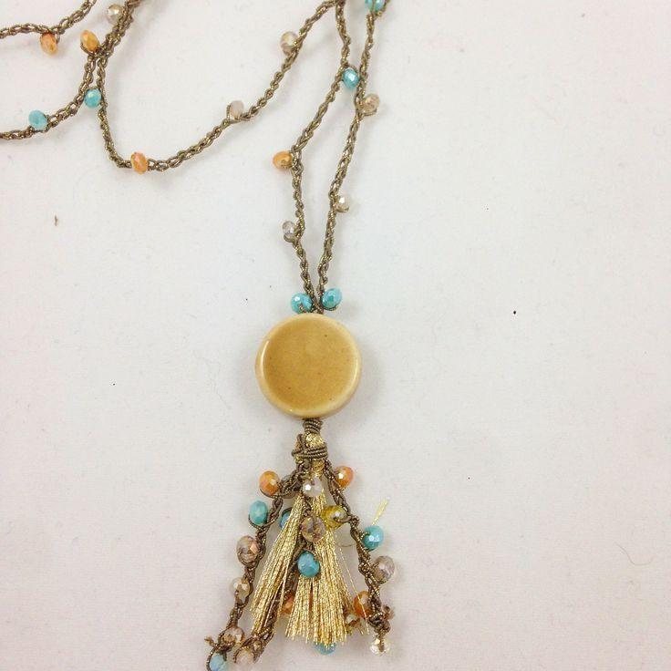 #collana all#uncinetto in #filato #metallizzato #oro con #charme in ceramica, nappina oro e perline di cristallo di varie tonalità