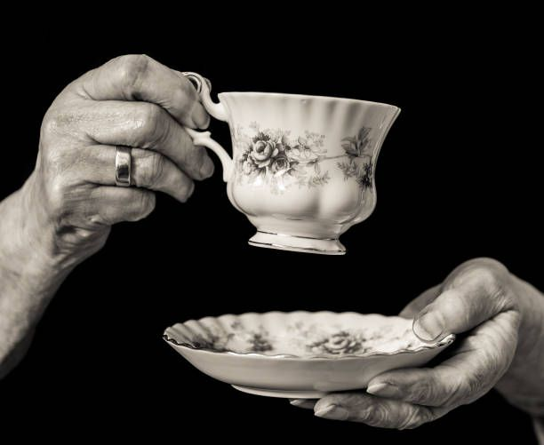 traditional teacup and saucer held in elderly womans hands