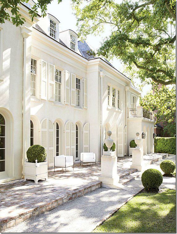 """Pamela Pierce's house is a warm white – with white shutters.  White on white with white furniture and urns that finish the look.""...2016"