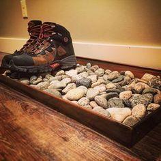 Legen Sie ein paar Steine für Ihre nassen Stiefel in ein Tablett.