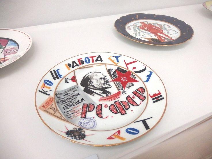 """Ausstellung """"Russische Avantgarde"""" Teller, collagenartig bemalt, am Rand mit bunten kyrillischen Buchstaben steht übersetzt: """" Wer nicht arbeitet soll auch nicht essen"""" von M.M.Adamowitsch"""