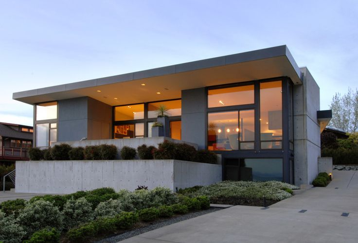 On a quiet, dead-end road in Edmonds, overlooking the Puget Sound, this house faces the Western view and southwestern storm fronts. Anchored with concrete walls, and protected with a deep roof overhang, the living room and dining area windows and doors expand to a large concrete terrace, surrounded by low, stepped retaining walls and a lush landscape. We will let owners Barbara & Don Berger tell the story...