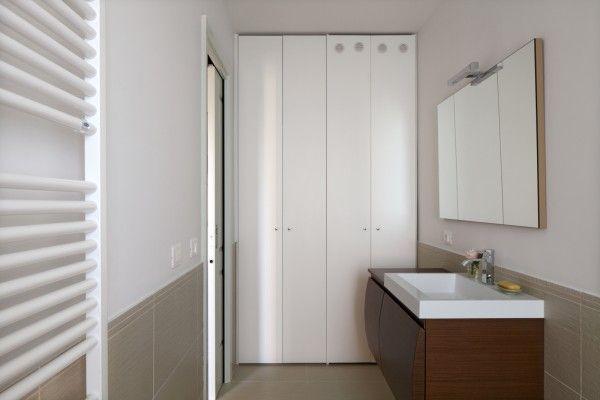 Dal lato opposto, di fronte alla doccia, è stato ricavato invece un vano lavanderia completamente nascosto da un'armadiatura