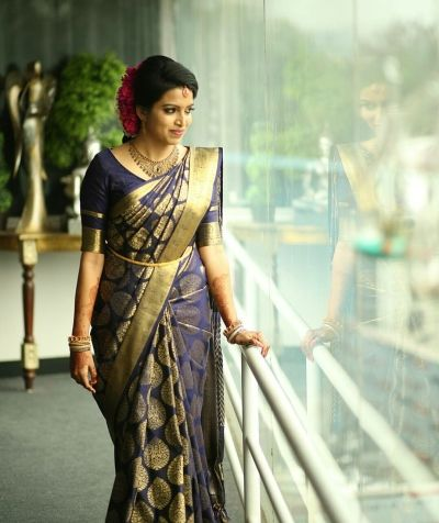 South Indian Bride - Bride in a Navy Blue and Dull Gold Saree with a Gold Waistbelt   WedMeGood #wedmegood #indianbride #indianwedding #bridalwear #southindianbride #saree #blueandgold #southindian