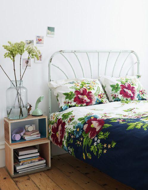 quarto simples e charmoso, com criado mudo de nichos e cama de ferro