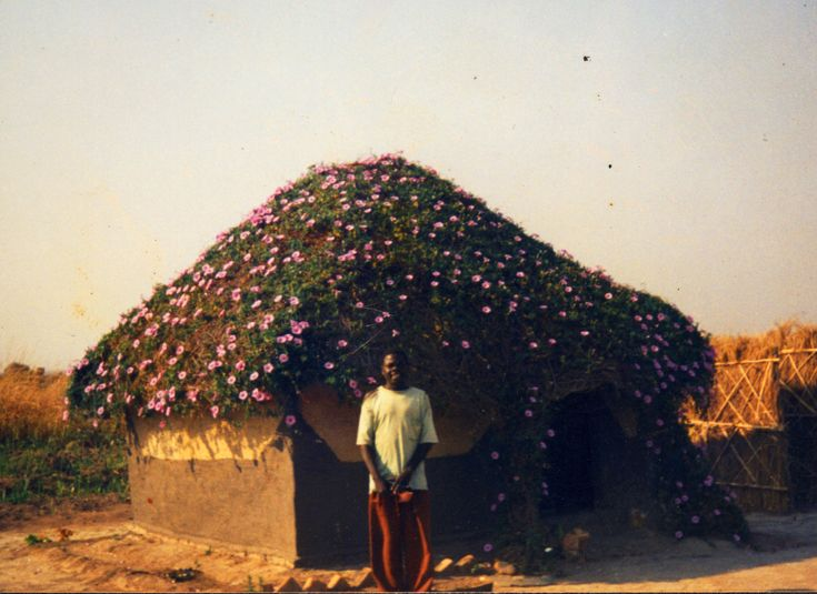 Zambia man standing in front of his home wit a roof for Architecture firms in zambia