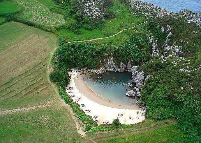 Playa de Gulpiyuri - Asturias. El agua entra a través del arrecife para formar una pequeña playa a unos cien metros del mar en el campo.