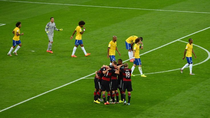 Sami Khedira of Germany celebrates with teammates scoring his team's fifth goal as Brazil players look dejected.