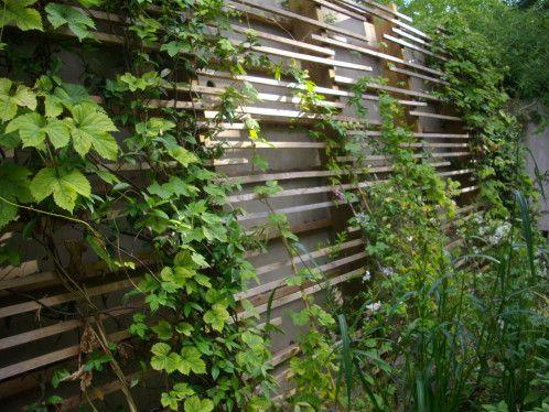Un treillage en bois moderne et facile  à construire. Des poteaux et  tasseaux de bois pour la structure. Une mise en place irrégulière sur les poteaux et vous voila avec une structure originale. Réalisable même par un non bricoleur. Une manière sympathique pour cacher un mur triste