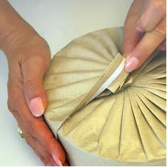 gift wrapping a circular tin with pleats