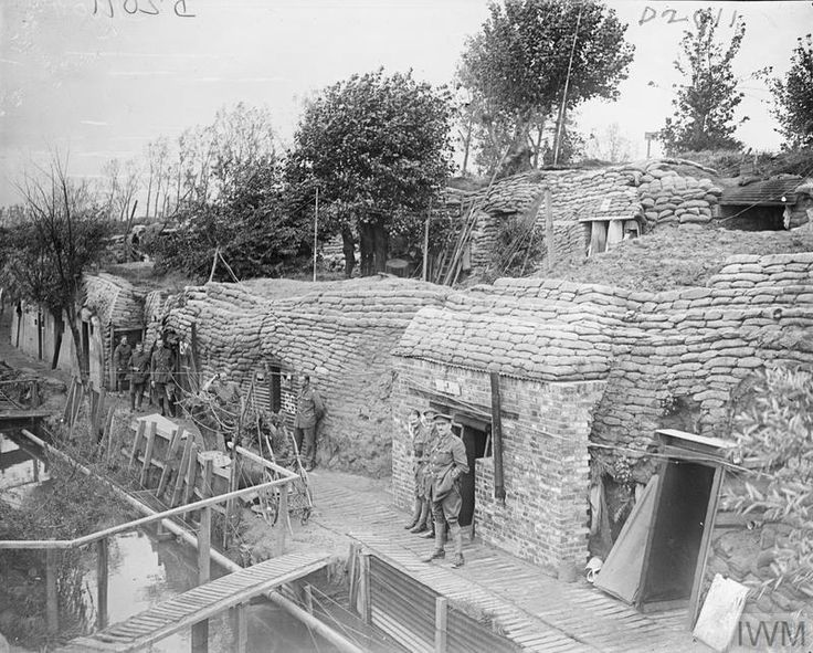WWI, 27 August 1917, Battle of Passchendaele; British officers outside their dug outs on the banks of the Yser Canal, Ypres. ©IWM Q 5947
