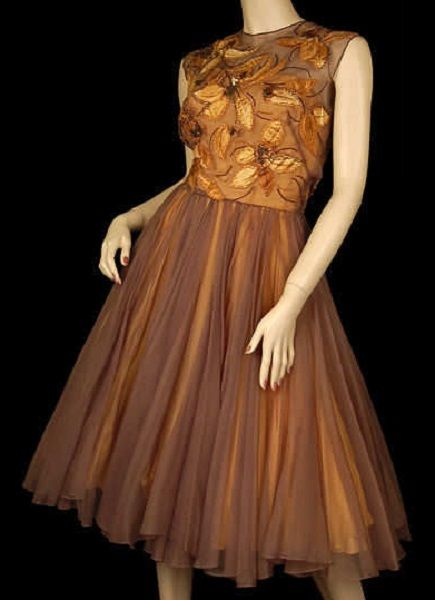 1950's cocktail party dress of sheer taupe brown silk chiffon. Full circle skirt gathered to a balloon bodice overlay, appliqued silk bodice with hand painted autumn leaves outlined in gold and brown beads, underskirt layer of gold silk chiffon with an inner gold silk crepe skirt.  By Harvey Berin, designed by Karen Stark.