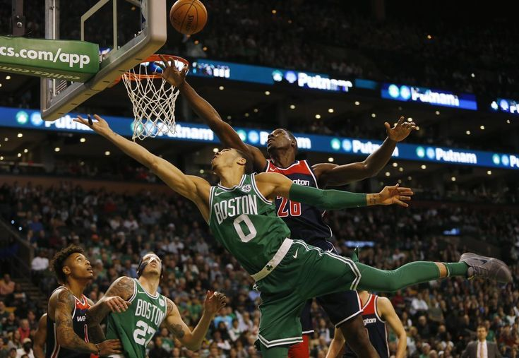 Boston, MA -- 12/25/2017 - Boston Celtics Jayson Tatum (L) drives to the net against Washington Wizards Ian Mahinmi during the second quarter of game action at TD Garden. (Jessica Rinaldi/Globe Staff) Topic: Reporter: