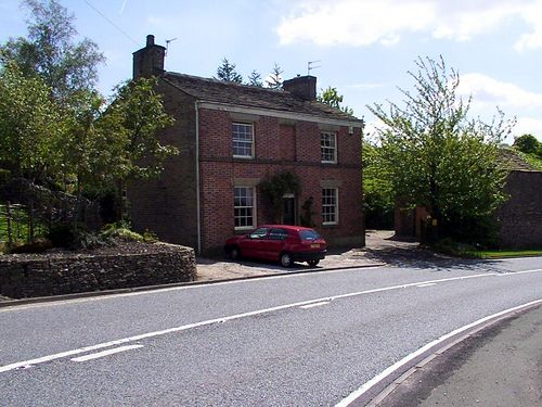 "New Inn Farm, early 19th century. ""This farmhouse originated as an inn. It is in brick with stone dressings, and has a Kerridge stone-slate roof. The house is in two storeys, and has a symmetrical three-bay front. The central doorway has a semicircular head with a fanlight, and a rosette carved in the keystone. The windows are sashes."" http://en.wikipedia.org/wiki/Listed_buildings_in_Rainow"