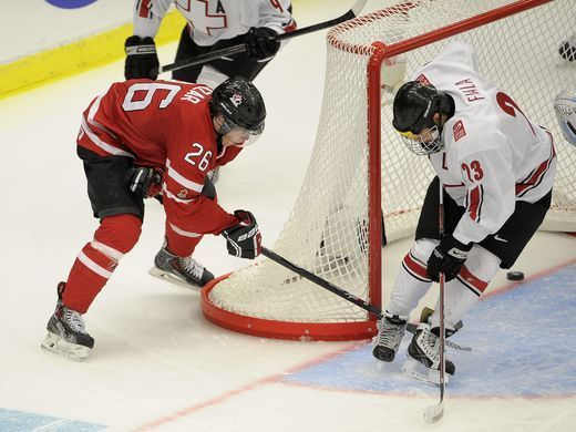 Canada's Curtis Lazar, left, manages to get the puck into the net behind Switzerland's Kevin Fiala during the World Junior Hockey Championships quarter final between Canada and Switzerland at the Malmo Stadium in Malmo, Sweden on Jan. 2, 2014. Canada won the match 4-1.