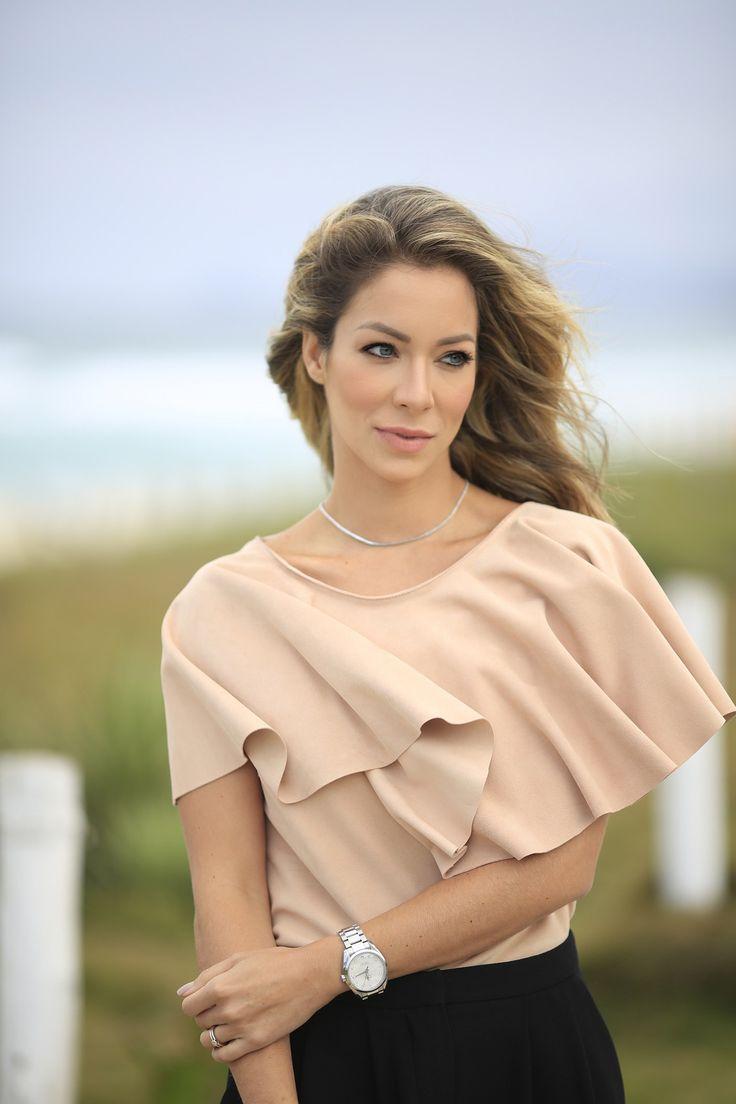Confira o look da Helena Lunardelli na praia: blusa bege com babados com bermuda preta e sandália rasteira.