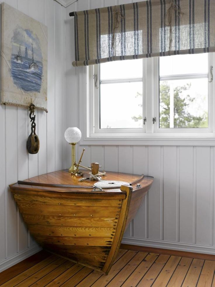 MARITIM KUNST:Veggene prydes av ulike maritime kunstverk. Dette bildet er malt av Smögen-kunstneren Nils Holm. Den gamle snekka fungerer som dekorasjon og praktisk sidebord.veggene er malt med Interior High Finish 20, glans 20, Gipshvit IN 582, tekstilene er fra Green Apple.