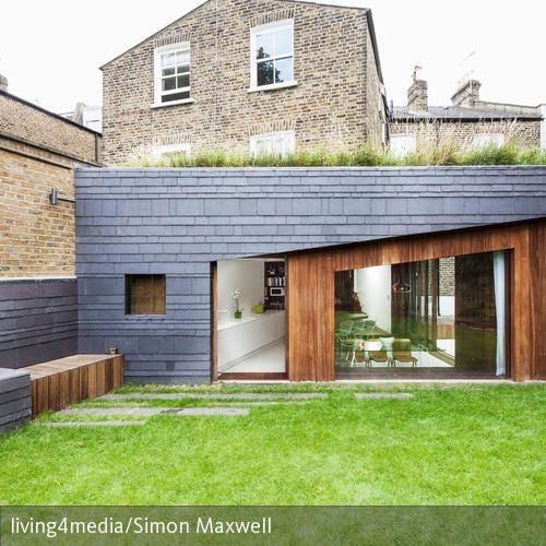 Der moderne Anbau an das traditionelle Backsteinhaus setzt einen interessanten Stil-Kontrast, fügt sich aber durch die klassischen Materialien Schiefer und…